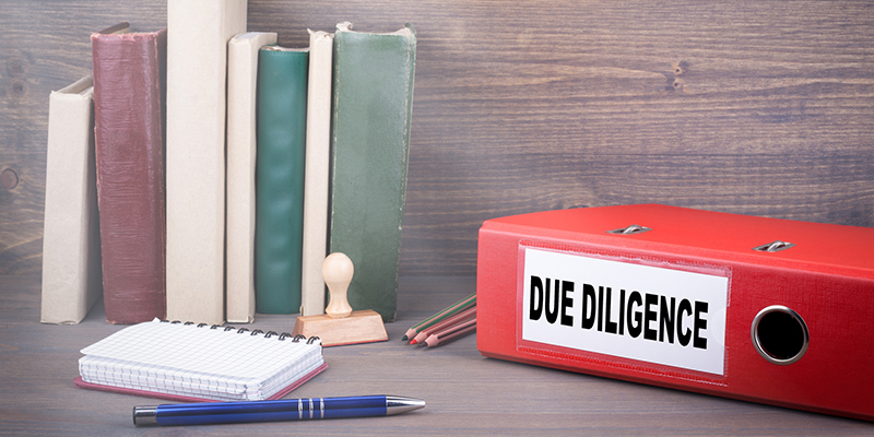 """Red """"Due Diligence"""" Binder on Office Desk with Pen and Paper"""