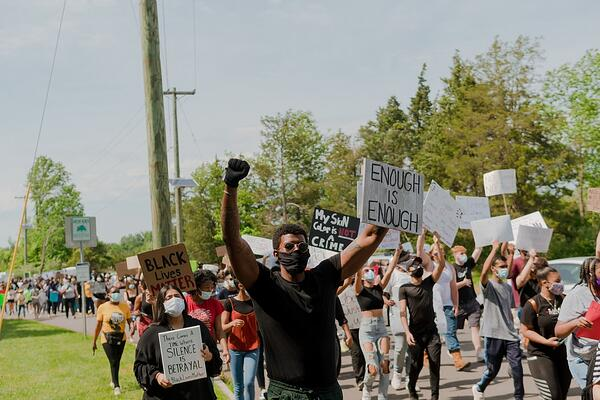 """Protesters march with signs reading """"enough is enough"""" and """"black lives matter"""""""