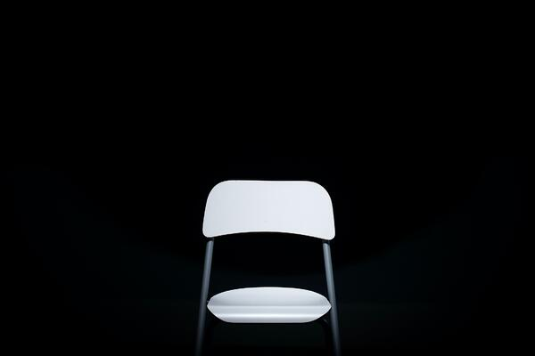 Blog header image: an empty white chair against a black background